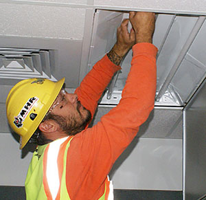 A man replace a light in commercial place