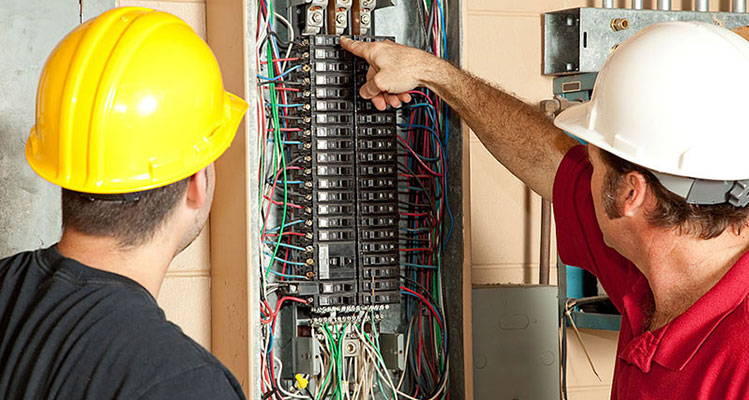 two electricians looking over a breaker box